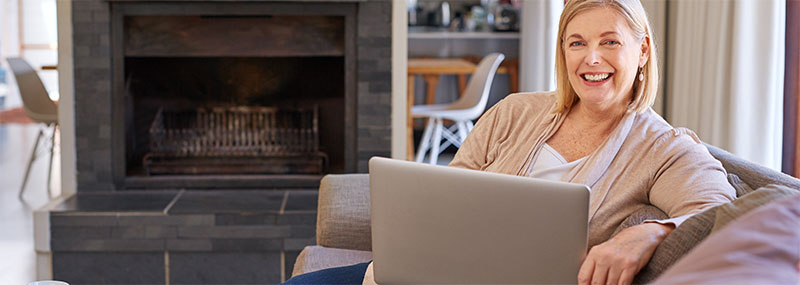 Older woman sitting at home, enjoying her EZ Link Internet access.